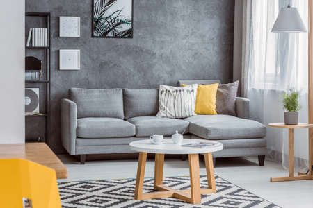 Spacious living room and open dining area with patterned rug, scandinavian coffee table, yellow pillow and canary chair