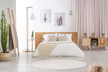 핑크 천으로 나무 찬 장으로 침실에서 흰 벽에 걸려있는 두 개의 간단한 포스터 스톡 콘텐츠