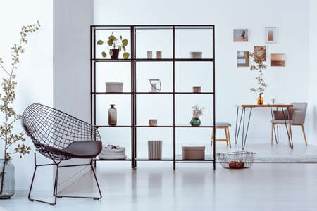 Black metal rack with books, plants, candles and decorations standing in a white room with metal chair