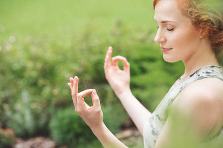 Young woman in harmony with nature practicing yoga in the garden Lizenzfreie Bilder