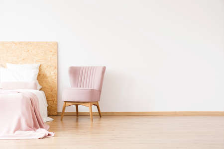 Elegant, pink chair standing next to a bed in a spacious bedroom interior