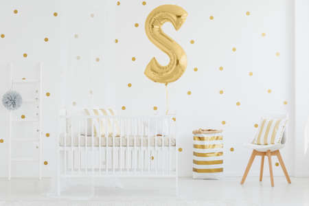 White and gold striped material basket placed in bright room with letter shaped balloon and tulle pompom on wooden ladder