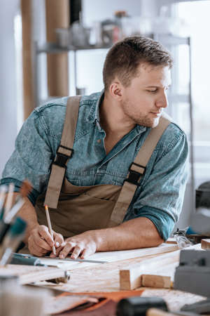 Young construction engineer sitting at desk and drawing on a wooden board
