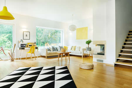 Geometric carpet on wooden floor of open space with pouf and corner sofa with pillows