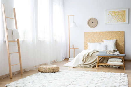Modern clock hanging over a double bed filled with pillows in a white bedroom interior