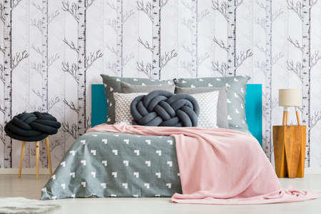 Pink blanket and knot pillow on king-size bed in bedroom with lamp on wooden stool
