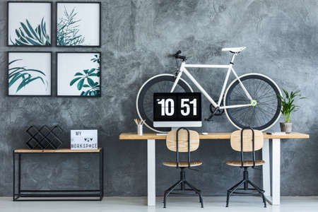 Black and white bicycle standing on wooden desk with computer and potted plant