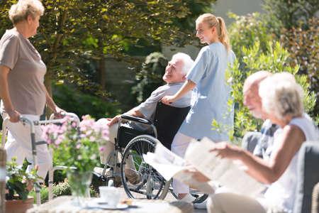 Verpleegster ondersteunend de hogere mens in een rolstoel tijdens vergadering met vrienden in de tuin op zonnige dag