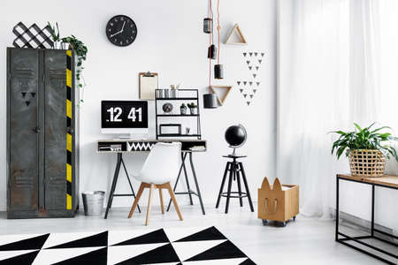 Black clock hanging on white wall above desk with computer standing next to old locker