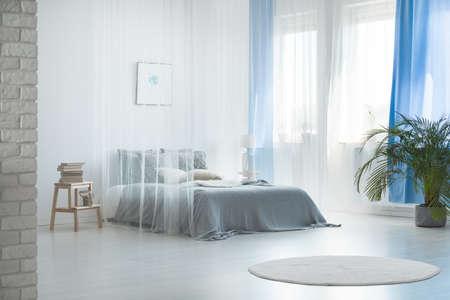 Gemütliche, romantische Inneneinrichtung eines geräumigen, hellblauen Schlafzimmers mit transparenten Vorhängen über einem bequemen Doppelbett