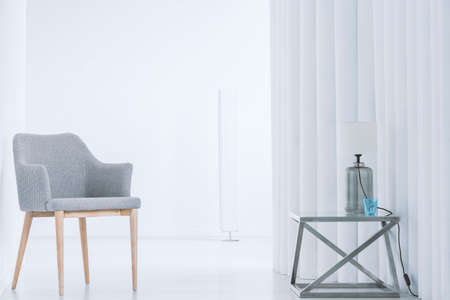 Grey chair and lamp on designer table against creative wall in white interior