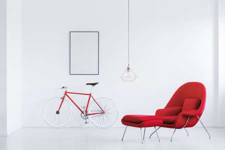 Mockup poster on white wall above red bike in white studio with red armchair and stool 版權商用圖片