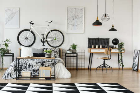Simple bright bedroom with fresh potted plants, posters and bicycle