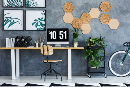 Wood and metal chair standing by the desk in living room with workspace Lizenzfreie Bilder