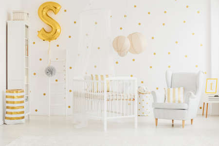 Grey armchair with striped cushion standing next to white crib with canopy in baby room Lizenzfreie Bilder