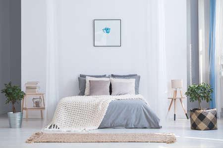 Rustgevend grijs en blauw kleurenpallet voor een uitgebalanceerde slaapkamer in een gezellig vlak interieur met planten en natuurlijke accessoires Stockfoto