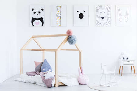 White rocking horse in child's bedroom with DIY bed and white cabinet against wall with posters Foto de archivo
