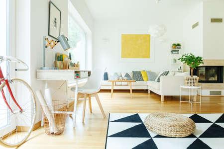 Pouf on black and white carpet near chair at desk in white living room with gold painting above corner sofa Lizenzfreie Bilder