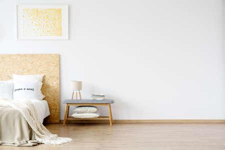 침대 위에 매달려있는 노란 그림과 램프가있는 작은 벤치와 침실 내부에 책 더미 스톡 콘텐츠