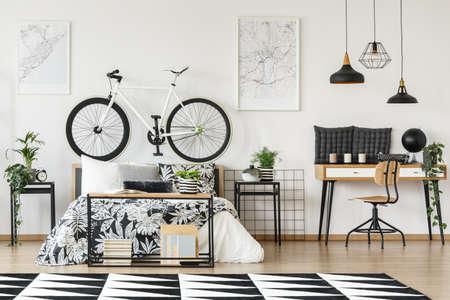 Black and white bike standing on wooden bedhead in bright interior Lizenzfreie Bilder