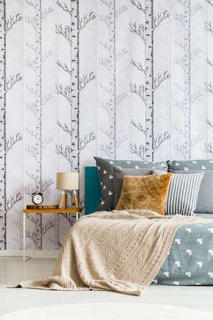 Beige blanket on king-size bed in simple bedroom with lamp and clock on nightstand Lizenzfreie Bilder