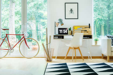 Red bicycle in open workspace with white chair at desk with laptop and designer lamp
