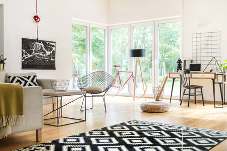 Open space living room interior with geometric carpet and study space with laptop