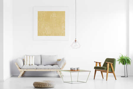 Gold painting above grey sofa in bright living room with armchair at table, pouf and fern