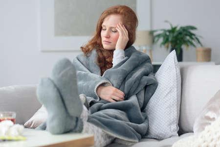 Sick woman with a headache sitting on a sofa at home wrapped in grey blanket Lizenzfreie Bilder