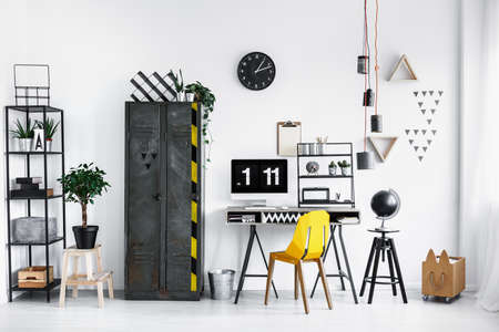 Black metal rack with potted plants and boxes standing in the corner of white industrial flat