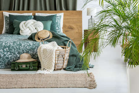 Blanket in basket and hat on luggage next to king-size bed with white pillow in bedroom Stock Photo