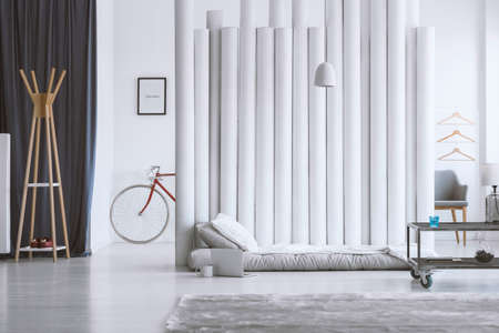 Wooden hanger in designer bedroom with grey mattress against screen and table on wheels