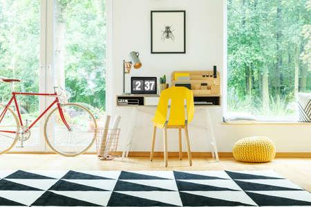 Yellow chair at desk with laptop between pouf on floor and red bike in bright workspace Lizenzfreie Bilder
