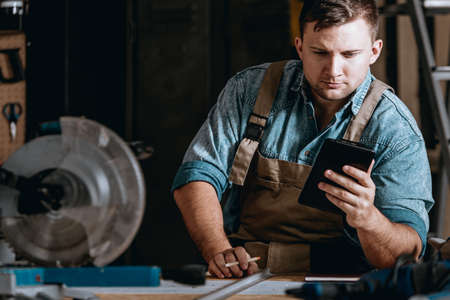 Self-employed machine constructor calculating costs while working at manufacturing plant