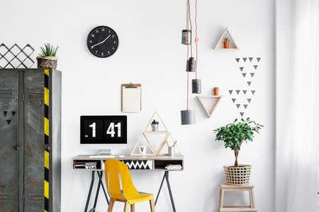 De met de hand gemaakte metaal kan lampenkap met het oranje draad hangen in witte bureauruimte met verse installatie en computermonitor op bureau