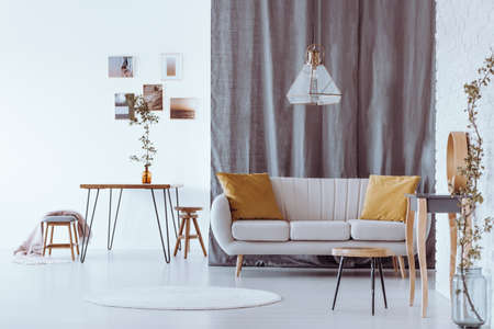Bright sofa with yellow cushions standing in stylish living room with hairpin table in the background