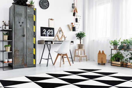 Black and white carpet with geometric pattern on the floor in modern home office in bright industrial flat