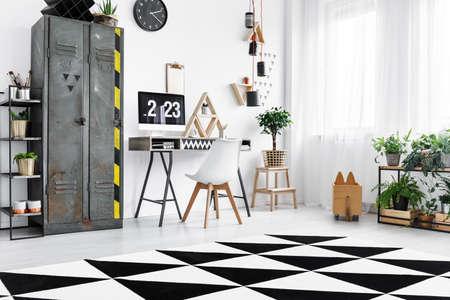 Zwart en wit tapijt met geometrische patroon op de vloer in moderne kantoor aan huis in lichte industriële flat Stockfoto - 90266044