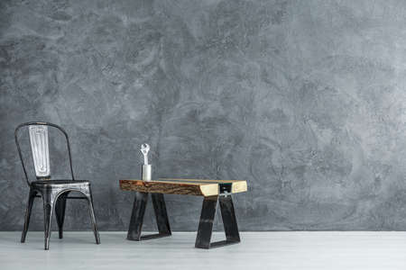 Black chair next to work table with tool in metal can against concrete wall in handymans dark room, copy space interior concept  Lizenzfreie Bilder