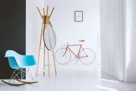 Blue designer rocking chair next to mirror on hanger in bright hall with red bike against wall with poster