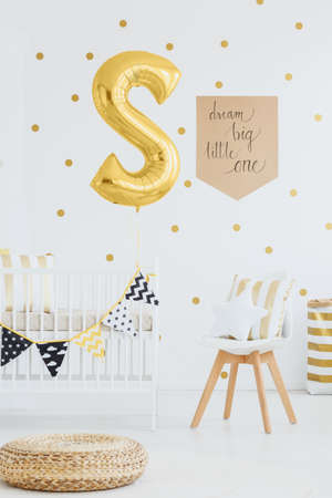 Round wicker footrest placed on the floor in white room for a baby with golden balloon and poster on the wall