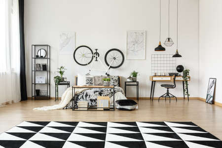 Big black and white carpet with geometric pattern on the floor in room with bed Lizenzfreie Bilder