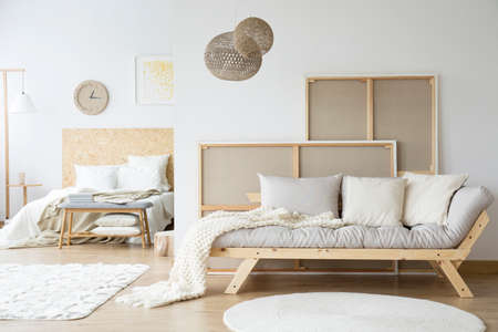 Kings-size bed and a cozy sofa in a monochromatic white room interior Banco de Imagens