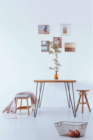 Framed photos hanging on a white wall in bright dining room with hairpin table, wooden stool, and velvet bench with blanket Lizenzfreie Bilder