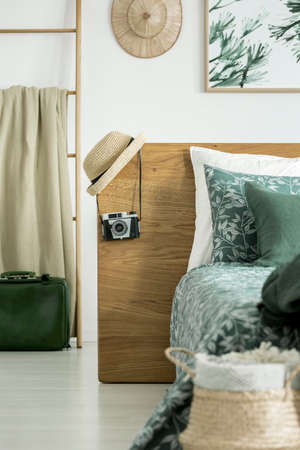 Hat and camera on headboard and blanket on ladder in bedroom with souvenirs Imagens