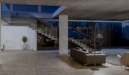 Side view of glass staircase in concrete house with big windows at night. 3D rendering.