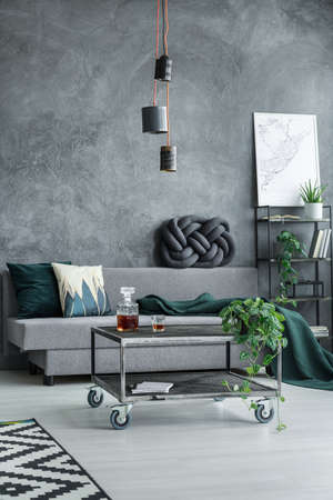 Designer lamp above table on wheels in monochromatic living room with grey sofa against textured wall