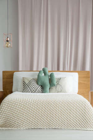 Pastel pink drape hanging behind bed with wooden bedhead and cactus shaped pillow Stock Photo