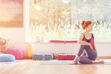 Red-haired woman sitting on mat at home with poufs and yoga equipment