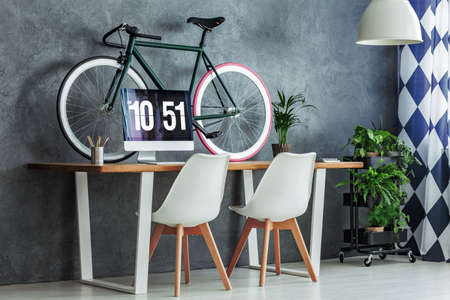 Fresh potted plants placed on a black metal trolley with wheels standing in the corner of a room with workspace